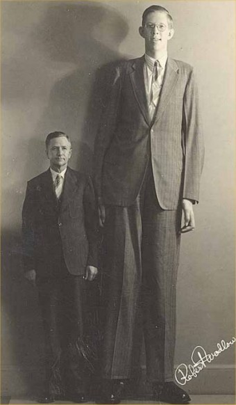"Robert Wadlow, the tallest man in recorded history, standing with his father of 5""11."