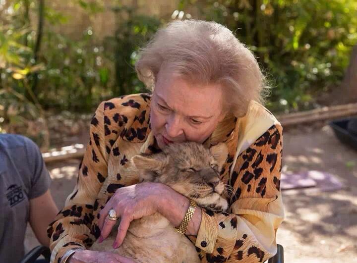 Betty White cuddling a lion cub.